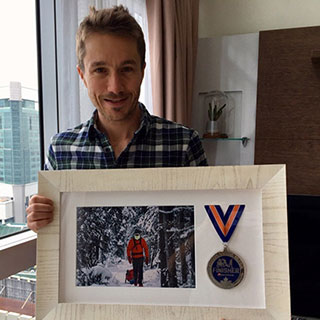 De Decker, at home in Singapore showing off his medal and photo from his race in 2018.