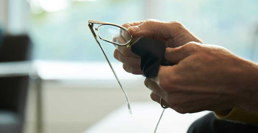 Man cleaning his glasses