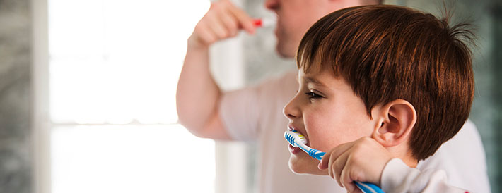 Boy brushing his teeth aside his parent