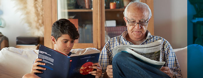 Grandfather and grandson reading book sitting on the couch
